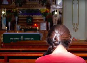 Mujer reza en capilla